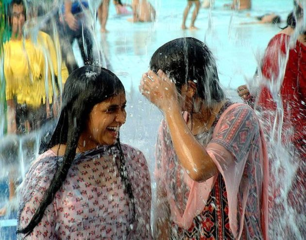 Girls smile as they enjoy a shower in a water park in the outskirts of Bhopal Madhya