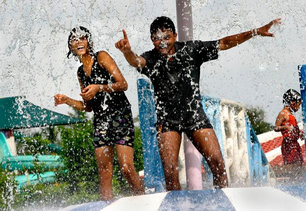 Young boys and girls cool down from the excessive heat in a water park in