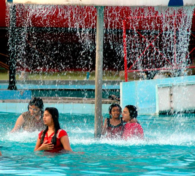 Indian women play in a water