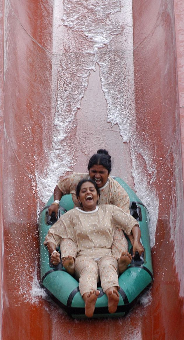 Two women on a water slide in the southern Indian state of Andhra