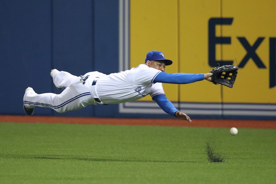 Ezequiel Carrera of the Toronto Blue Jays dives but cannot get to a single hit by Jett Bandy of the Los Angeles Angels of Ana