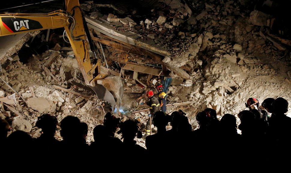 Rescuers work in the night at a collapsed house following an earthquake in Pescara del Tronto in central Italy. (Aug. 24, 201