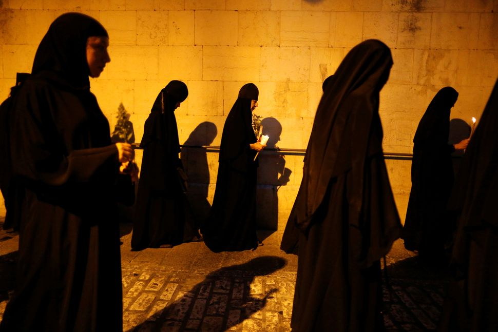 Orthodox Christian nuns take part in an annual procession along the Via Dolorosa in Jerusalem's Old City, during which an ico