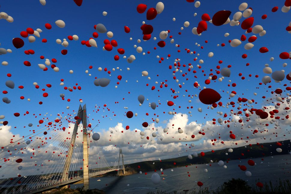 Red and white balloons are released during the opening ceremony of newly built Yavuz Sultan Selim bridge, the third bridge ov