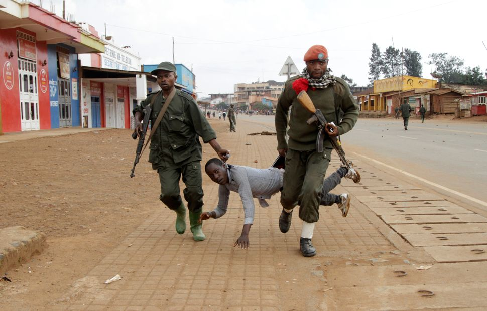 Congolese soldiers arrest a civilian protesting against the government's failure to stop the killings and inter-ethnic tensio