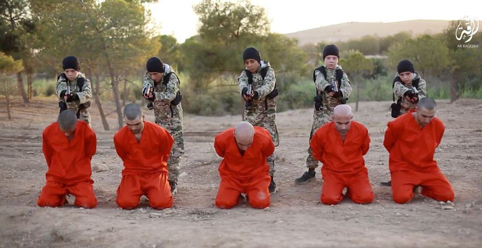 Children in fatigues are seen shooting prisoners in the ISIS