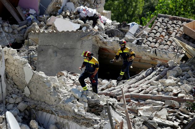 Firefighters inspect damaged houses following an earthquake in Pescara del Tronto, central Italy, August...