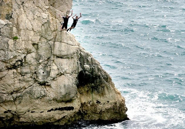 Two men jump off rocks into the sea at Durdle Door near West Lulworth,