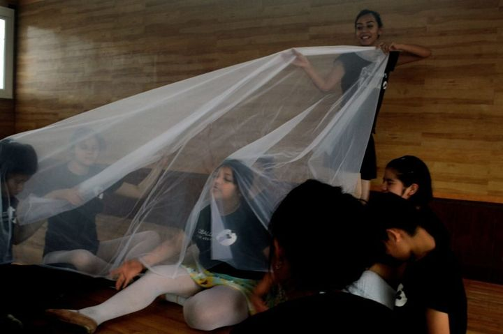 Teacher Lorena Nieva uses translucent fabric in an improvisation and games session in Mexico City to simulate the waves in a