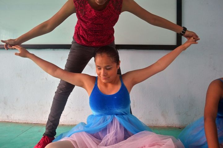 Nieva guides Patis arms in a lastminute stretch before the group is called out for their first dance at La Rosa School in Chi