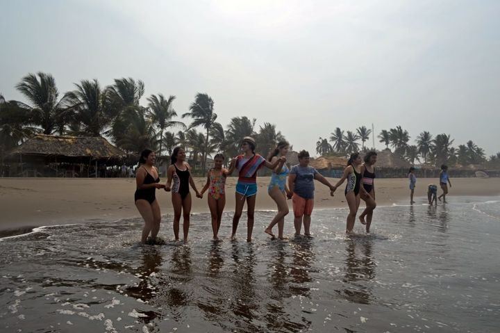 Nieva guides the girls into the sea at Puerto Arista beach in Chiapas.