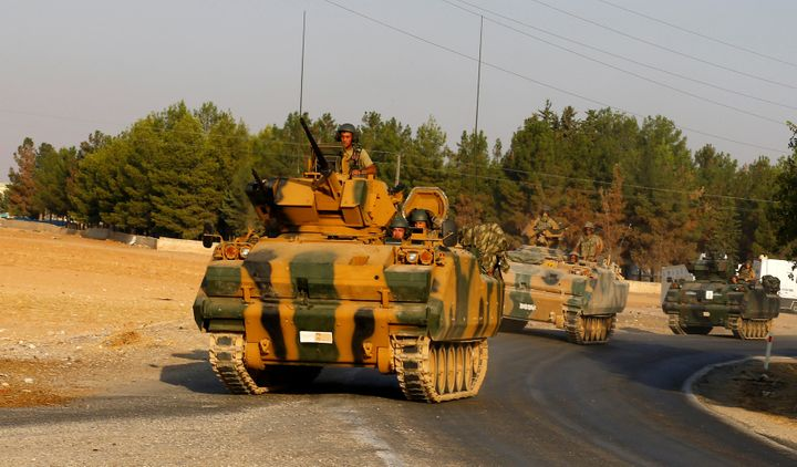 Turkish armoured personnel carriers drive towards the border in Karkamis on the Turkish-Syrian border in the southeastern Gaz