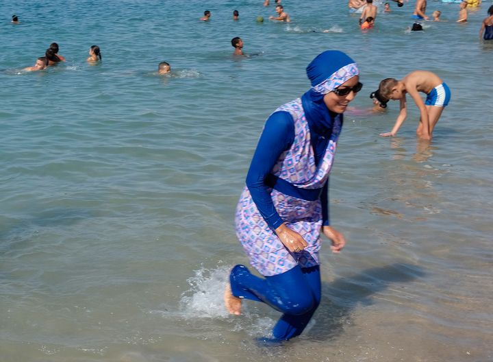 A woman wearing a burkini walks in the water August 27, 2016 on a beach in Marseille, France, the day after the country's hig