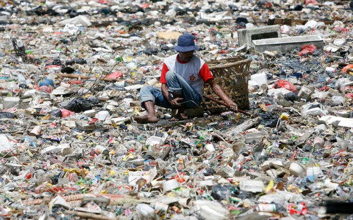 A man collects plastic goods in a river littered with garbage in Jakarta.