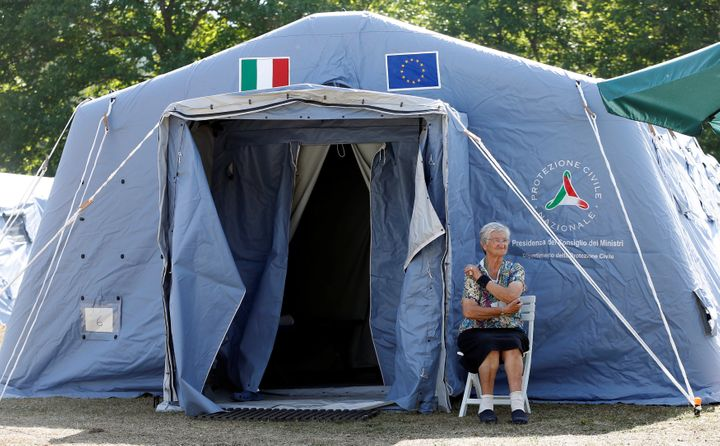 A woman sits outside a tent camp set up as a temporary shelter following an earthquake in Amatrice, central Italy.