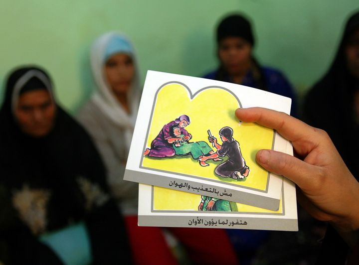 A counsellor holds up cards used to educate women about female genital mutilation (FGM) in Egypt, June 13, 2006. FGM is
