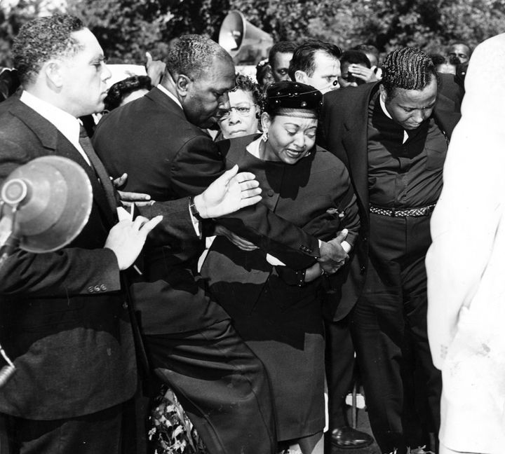 Mrs Mamie Bradley (center) reacts as the body of her son, Emmett Till, is lowered into his grave during the funeral, Septembe