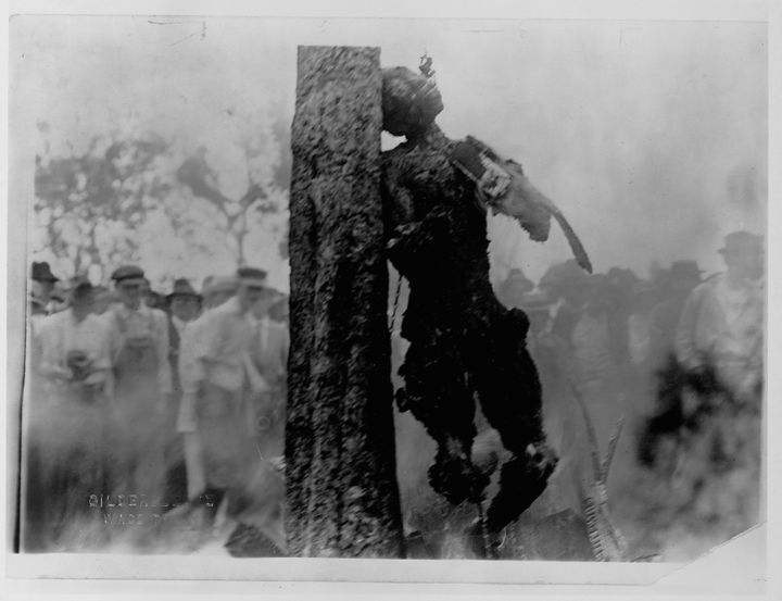 A crowd of people stands to watch the lynching by burning of Jesse Washington whose charred corpse leans chained to the trunk