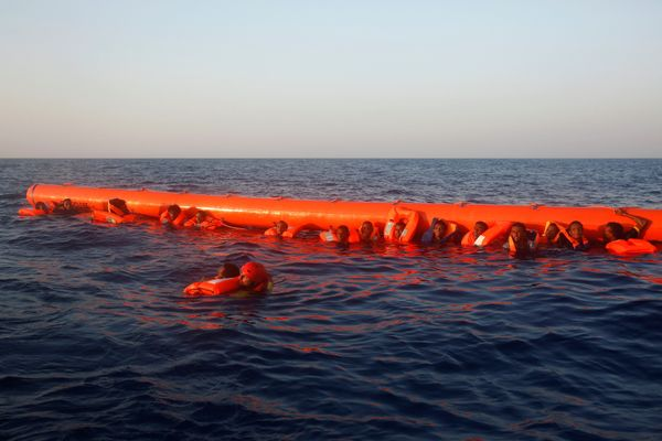 An air workerrescues a migrant from Eritrea as others cling to a floatation rescue device.