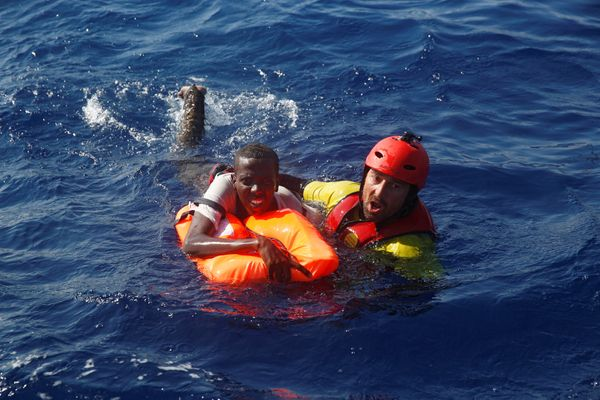 A member of the Spanish NGO Proactiva rescues a Somali migrant who fell from an overcrowded dinghy on Sunday.