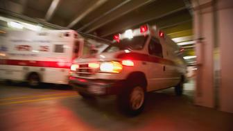 Ambulance pulling away from hospital (blurred motion)