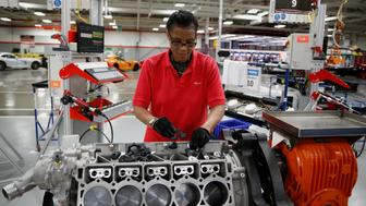 An employee works on the engine of a Fiat Chrysler Automobiles NV 2015 Dodge Viper vehicle on the production line at the FCA US Conner Avenue assembly plant in Detroit, Michigan, U.S., on Friday, May 8, 2015. Fiat Chrysler Automobiles NV sales in the U.S. rose 5.8% for April. Photographer: Jeff Kowalsky/Bloomberg via Getty Images