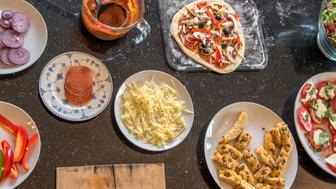 A range of pizza toppings laid out for a make your own pizza party