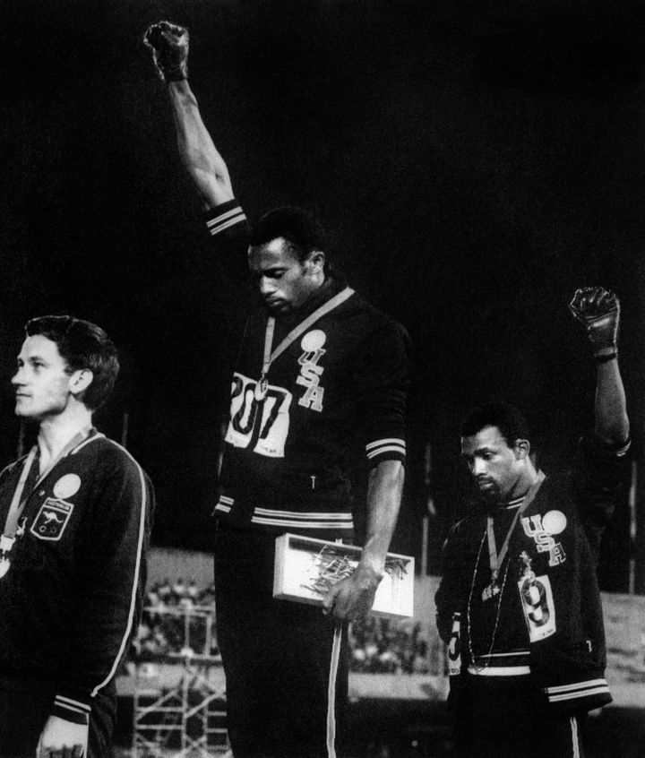 U.S. athletes Tommie Smith (C) and John Carlos (R) raise their gloved fists in solidarity with human rightsto express t