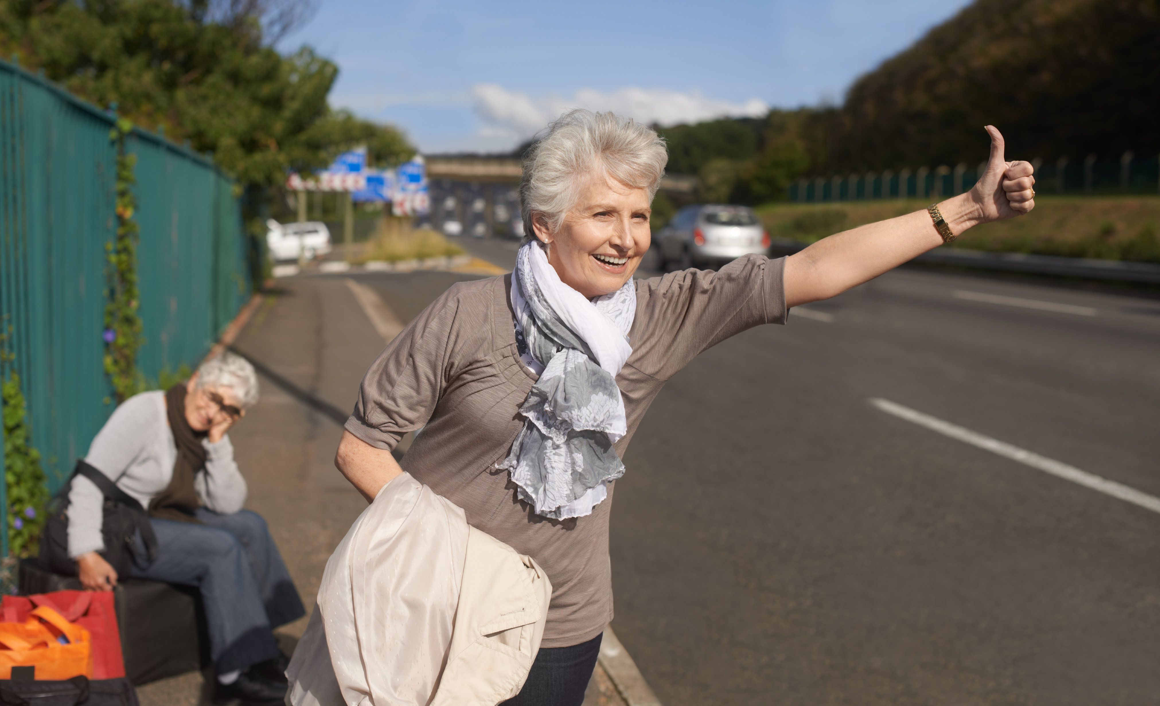 Two senior ladies hitch-hiking by the side of the road