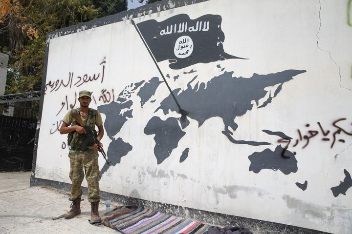 Soldiers write with a spray paint on a wall in support of Free Syrian Army in Jarabulus District of Aleppo