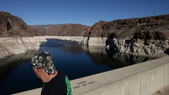 In this Wednesday, Oct. 14, 2015 photo, a tourist looks at Lake Mead on the Colorado River at Hoover Dam near Boulder City, Nev. The bathtub ring shows how far water level has dropped in recent years. (AP Photo/Jae C. Hong)