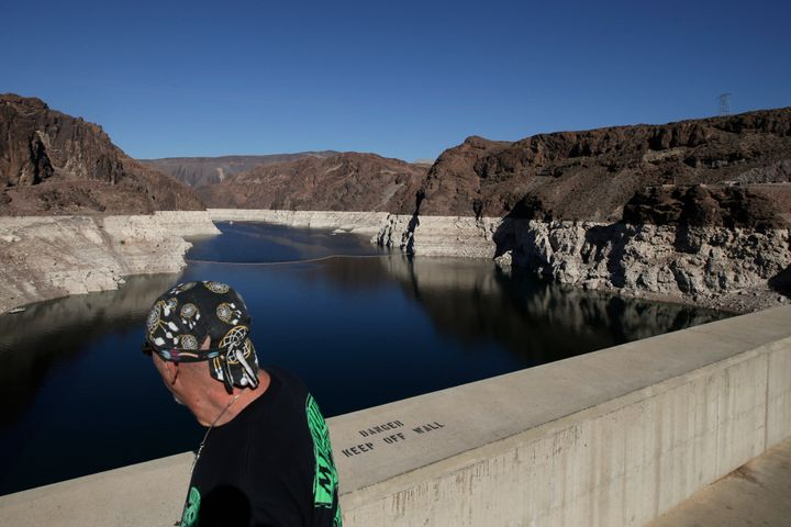 A tourist looks at Lake Mead on the Colorado River near Boulder City, Nev. While the lake's water level has dropped