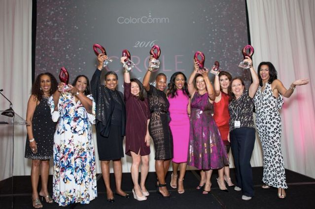 This year's ColorComm conference attendees stand onstage to celebrate their accomplishments.