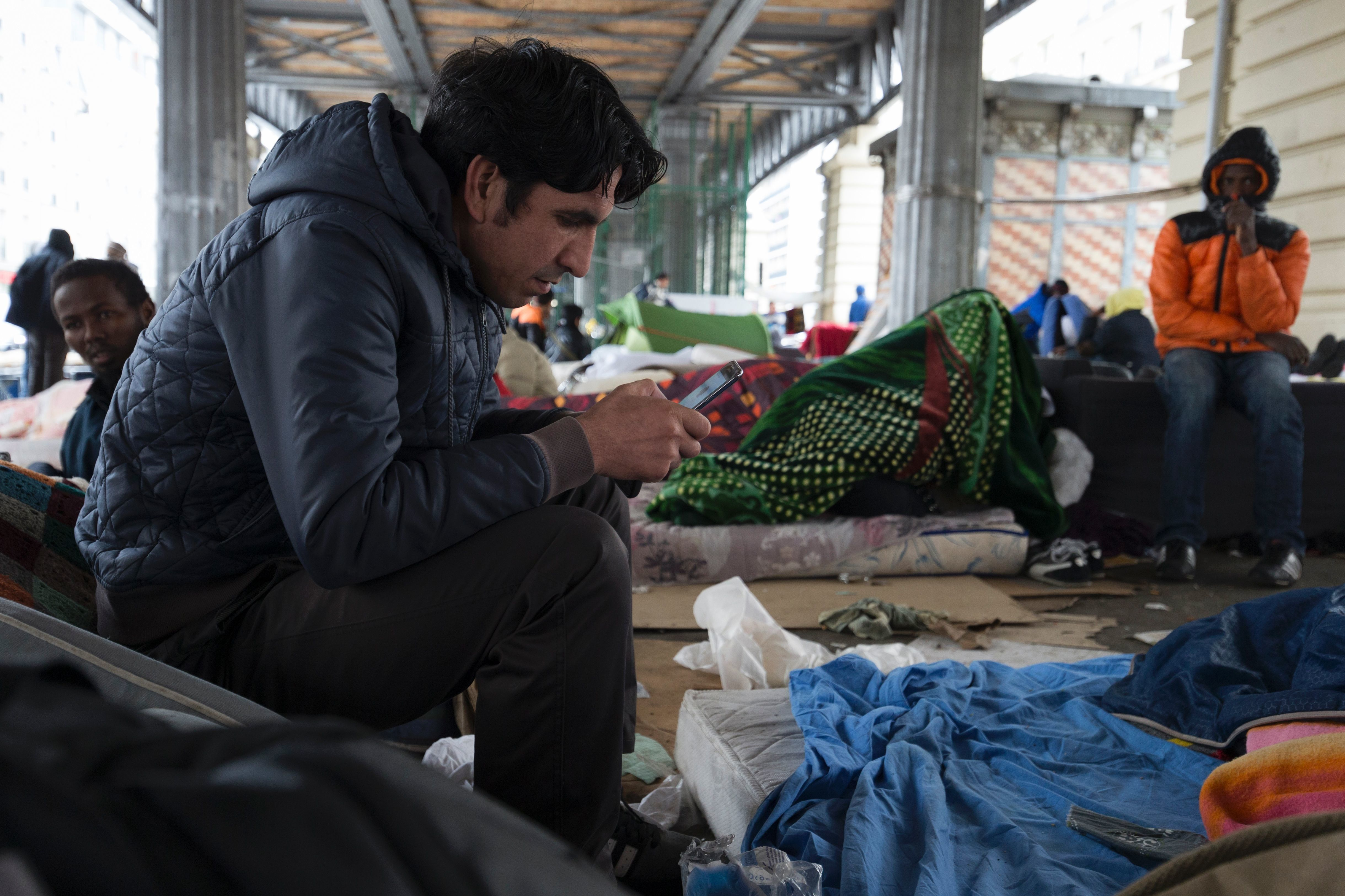 An Afghan migrant checks his mobile phone in a makeshift camp of refugees and migrants from Afghanistan, Sudan, Somalia, Erytrea, set under the Paris elevated railroad near the Stalingrad subway station on March 24, 2016. More than 100,000 migrants crossed the Mediterranean Sea in the first two months of 2016 alone, according to the United Nations High Commissioner for Refugees (UNHCR). / AFP / JOEL SAGET        (Photo credit should read JOEL SAGET/AFP/Getty Images)