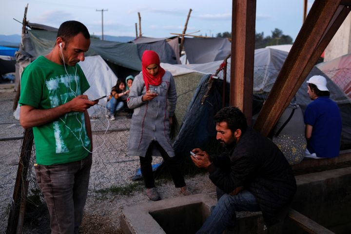 People use their mobile phones near a Wi-Fi hotspot at a makeshift camp for refugees and migrants near Idomeni, Greece, May 1