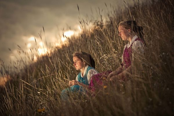 Sisters Elaine and Alice spending the evening together on the side of a hill overlooking the river.