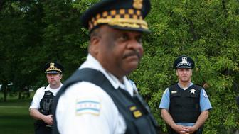 A police sergeant, left, and officer, right, watch as Chicago police Superintendent Eddie Johnson addresses the news media on police coverage for the Fourth of July weekend at Washington Park in Chicago on Monday, July 4, 2016. (John J. Kim/Chicago Tribune/TNS via Getty Images)