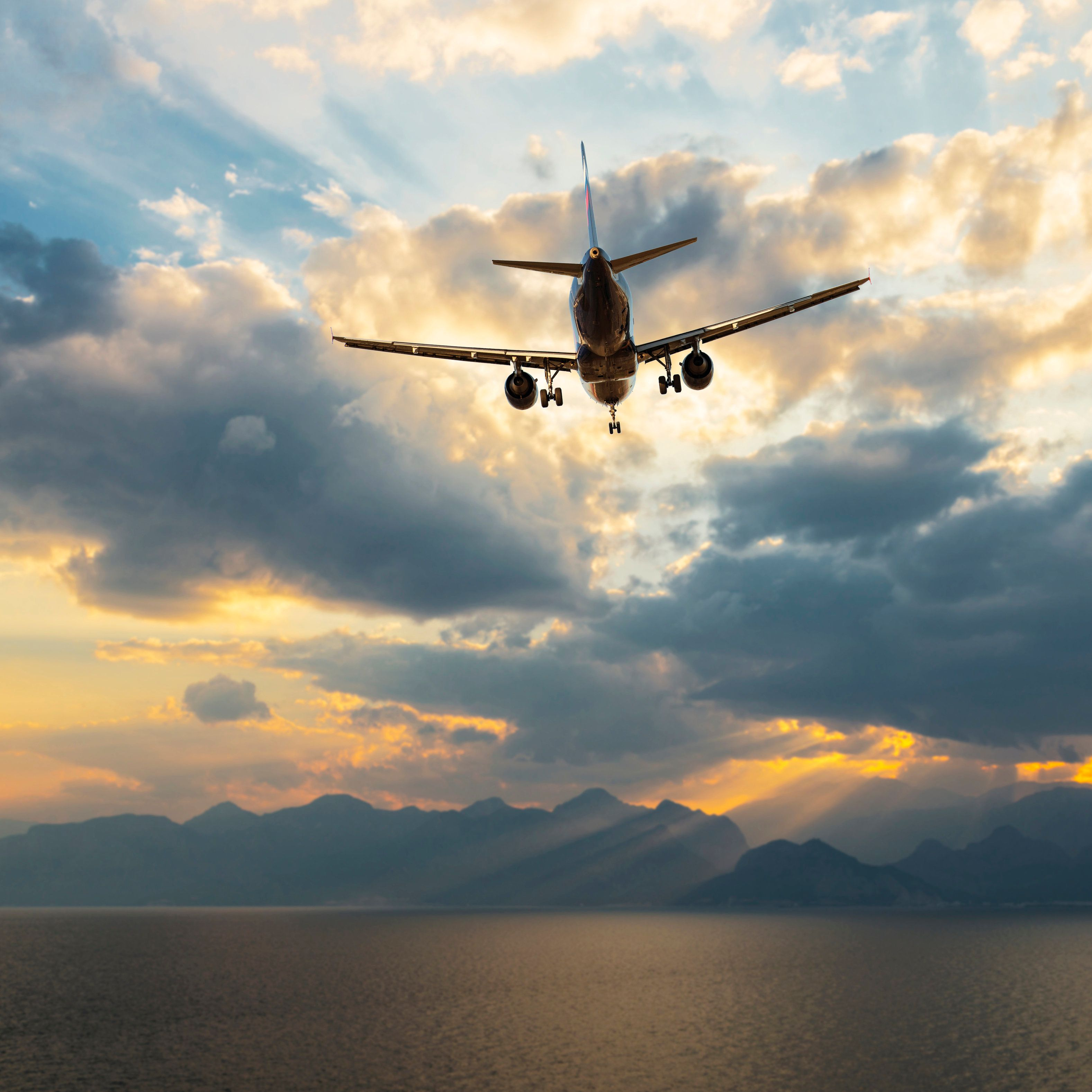 Airplane taking off over sea at dawn, near Antalya, Turkey.