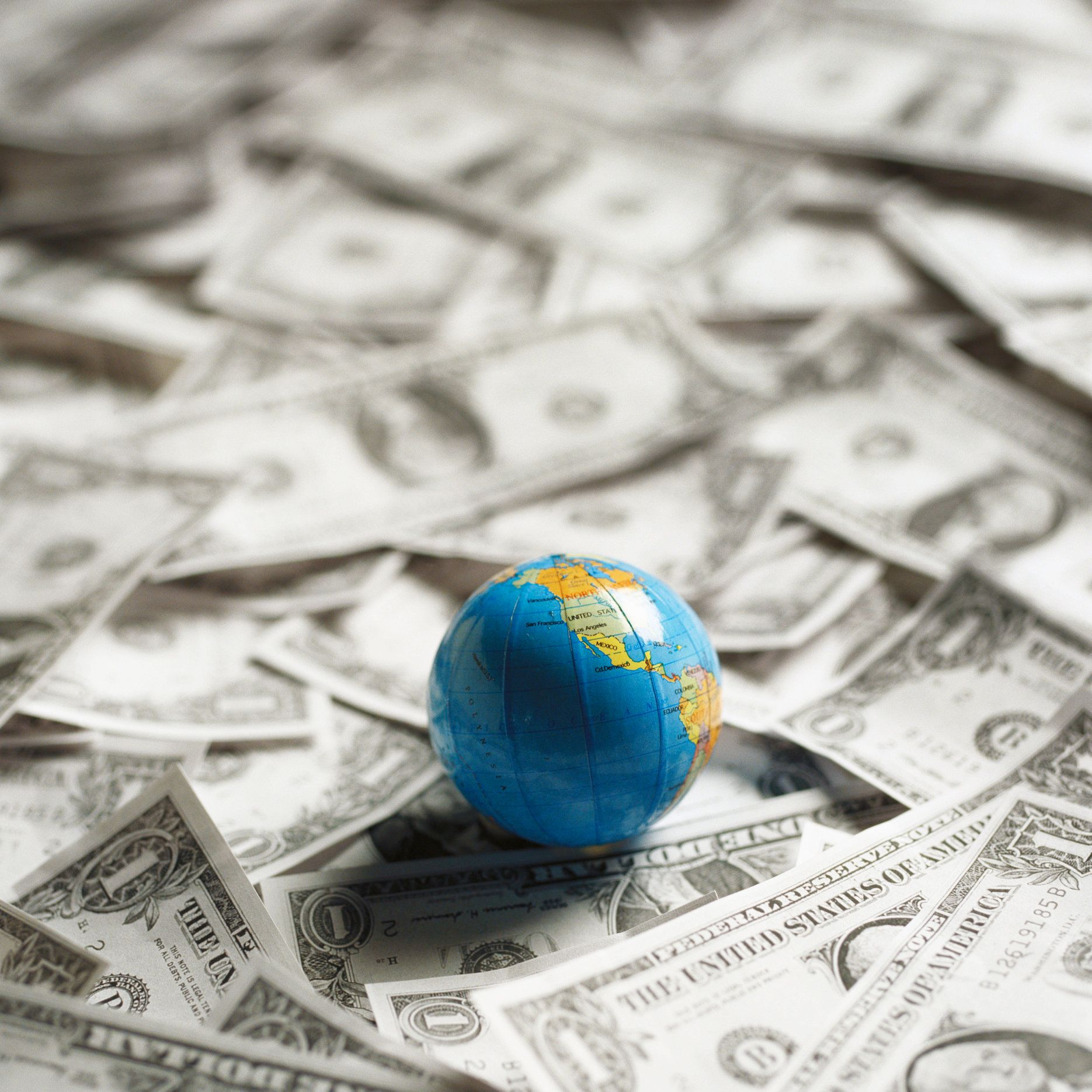 Small world globe on top of U.S. Dollars.