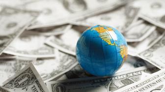 Small world globe on top of U.S. Dollars.