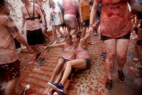 Participants sit on the floor, which is covered in tomato pulp.