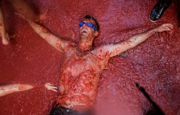 A reveller lies in tomato pulp during the annual Tomatina festival in Bunol near Valencia,