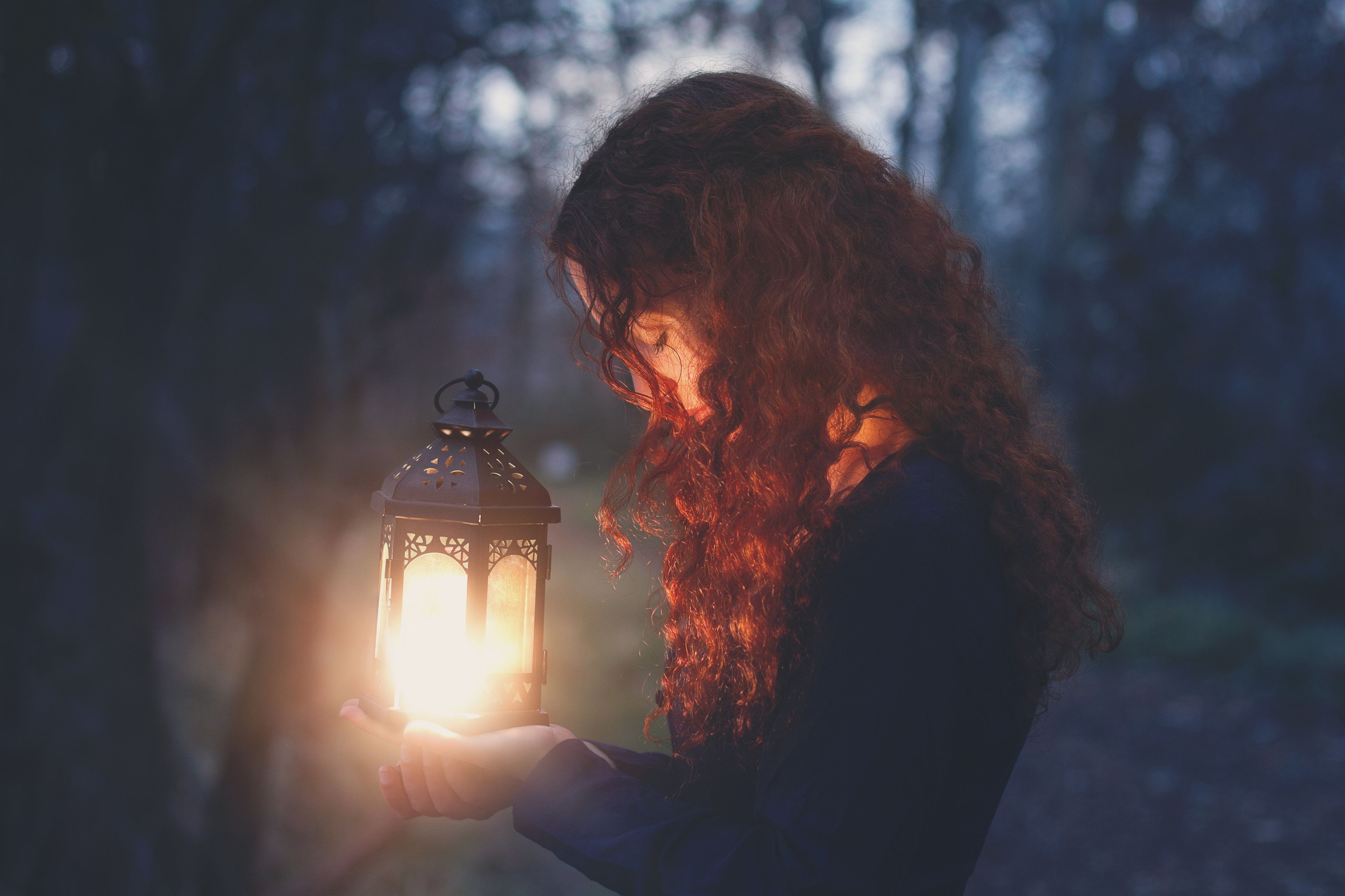 Young woman with long curly red hair wearing long-sleeved blue dress stands in profile with head bowed and eyes closed, holding small illuminated iron lantern with both hands outdoors in forest at dusk.