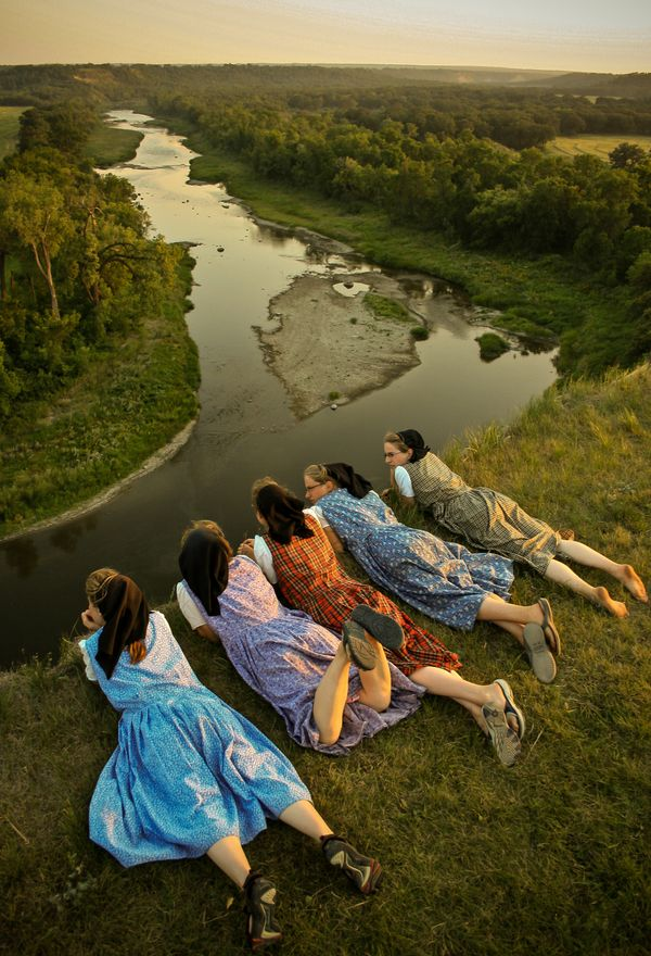 Hutterite women on a cliff overlooking the surrounding land.