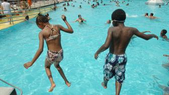 UNITED STATES - AUGUST 03:  Cousins Daysiah Smith (L.), 7, and Jahmel Binns (R.), 9, take a leap in the water together at Sol Goldman pool in Red Hook on a hot Friday afternoon.  (Photo by Linda Rosier/NY Daily News Archive via Getty Images)