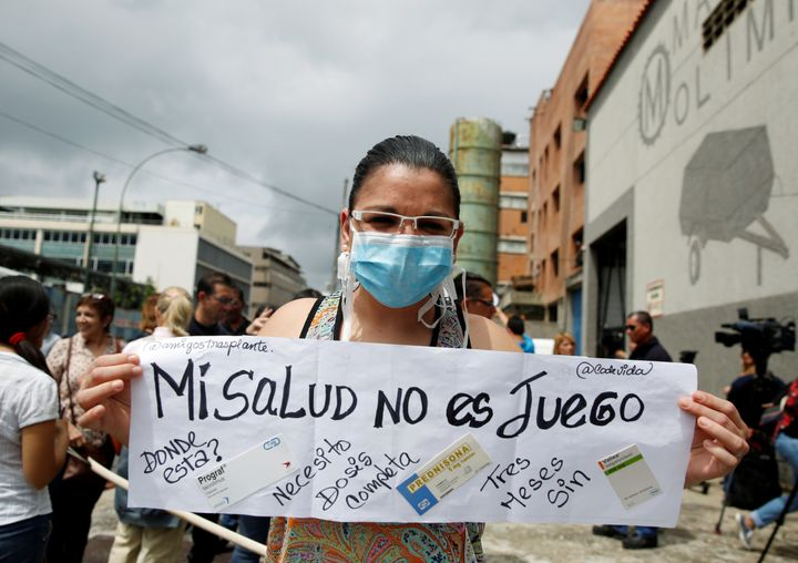 Natasha Suarez, a kidney transplant patient, holds a sign reading 'My health is not a game' during a protest outside a pharma