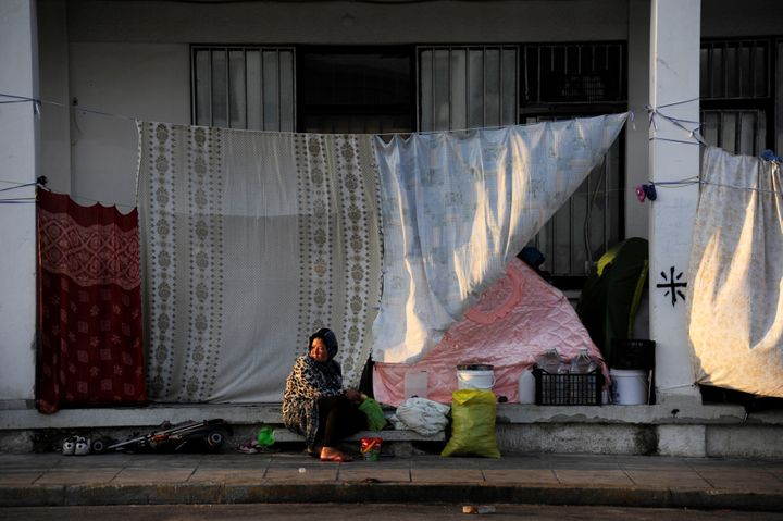 A woman sits outside a building covered with sheets to protect the dwellers from the strong summer sun outside of the Ellinik