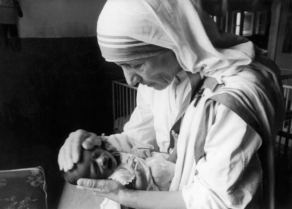 The Catholic missionary Mother Teresa trying to calm down a newborn orphan, by placing her hands on his head, in a clini