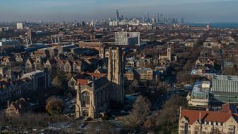 Aerial of Rockefeller Chapel a Gothic Revival chapel on the campus of the University of Chicago with Chicago city skyline in the distance, Illinois