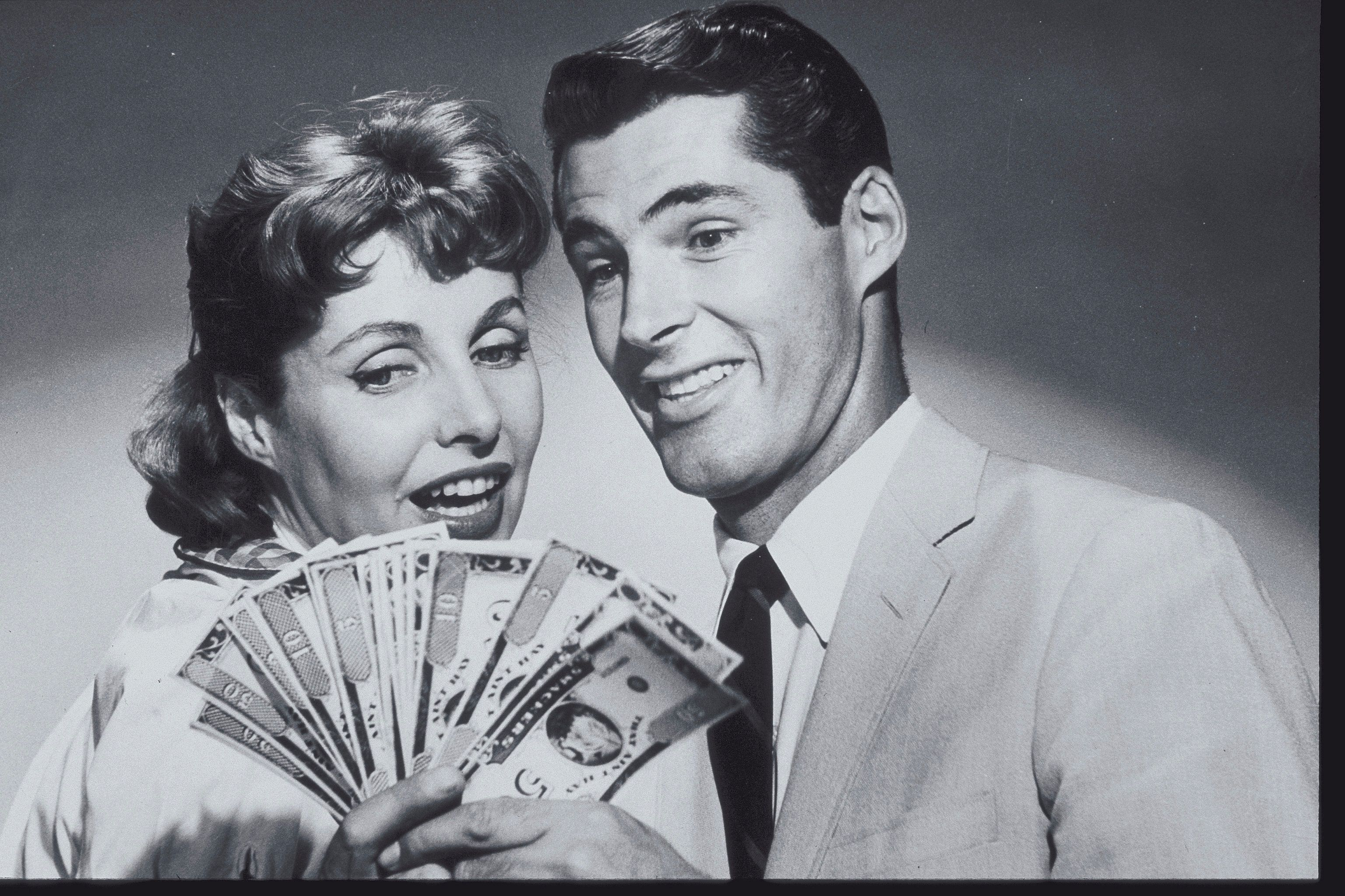 COUPLE SMILING AT A SPREAD OF MONEY